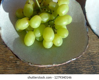 Green bunch of grapes on rustic tableware