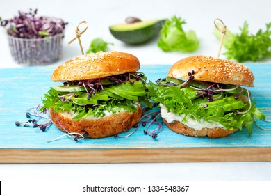 green burger with avocado, cucumber, cream cheese and micro greens on a blue board