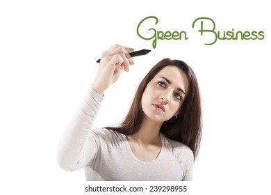 Green business. Sustainability. Beautiful girl presenting and writing the word green business on white board, looking toward the camera.