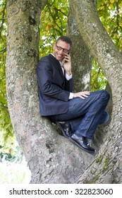 green businessman - fun businessman thrilled to be up in a tree for peace and protection from nature, calling from his cell phone with happiness