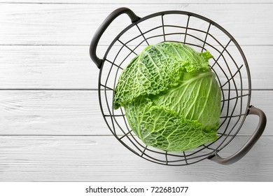 Green cabbage in metal basket on table