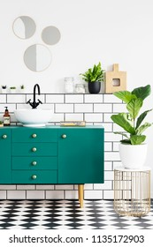 Green cabinet next to plant on gold table in modern bathroom interior with mirrors. Real photo