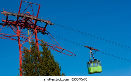 Green cable car speeding upwards. Some fir trees seen lower left.