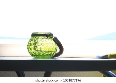 green candle holder on a table with seaside background