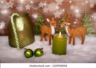 a green candle with reindeer and bambi in the snow, wooden background with bokeh effects