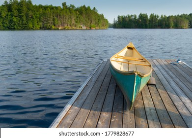 Green canoe rest on a lake wooden pier on a sunny summer day at the cottage. A wood pier is visible across the water.
