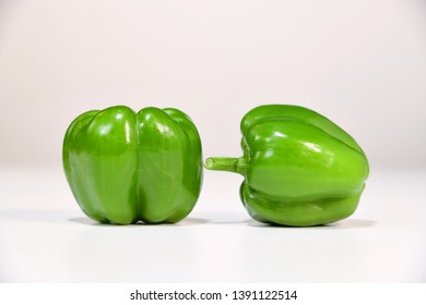 Green capsicum against white background. The capsicums are fresh and appetising.