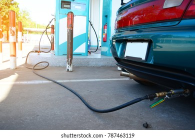 the green car and sun light in the gas LPG station with the black rubber tube from the fuel supply unit