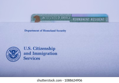 Green card (USA Permanent resident) under Envelope from USCIS (Department of homeland Security - United States Citizenship and Immigration Services). White Background. Official department Logo.