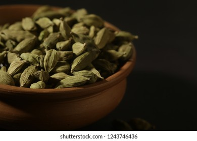 green cardamom on dark background, cardamom in earthen bowl
