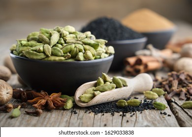 Green cardamom pods in black ceramic bowl in the foreground. Aromatic spices: anise, gloves, black cumin seeds, nutmegs, cinnamon sticks, turmeric. Ingredients for cooking. Ayurveda treatments.