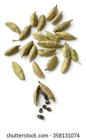 Green cardamom pods and seeds on white background