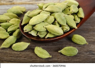 green cardamom pods  in wooden spoon