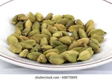 Green cardamom seeds or pods placed in a white ceramic plate