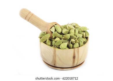green cardamom in wooden cup isolated