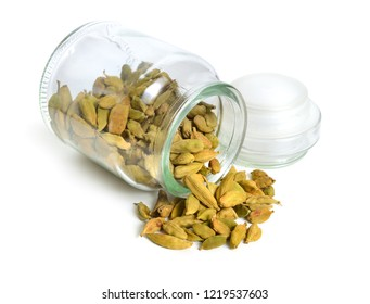 Green cardamon seeds in glass jar isolated on a white background