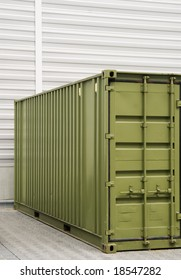 green cargo container in front of a wall