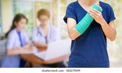 Green cast on an arm of a women on blurred two female doctor with stethoscope, clipboard and Laptop on desk,Doctor working in clinic writing a prescription,  Health care and medical concept.