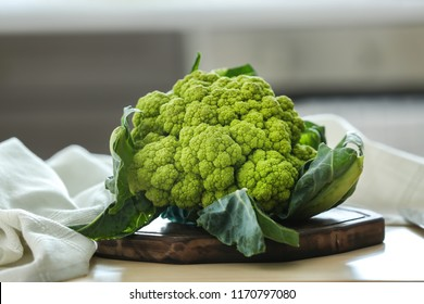 Green cauliflower on wooden board