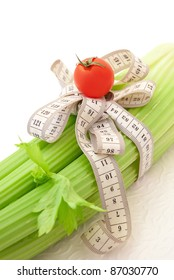 Green celery with tomato and tape measure, concept of healthy food and diet