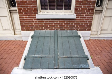 Green cellar doors outside a brick home, under a window.