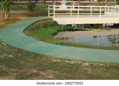 Green cement corridor in the park by an outdoor pond