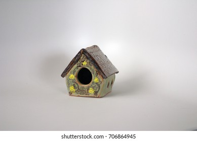 Green ceramic fairy garden house with a shiny brown roof