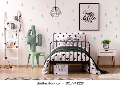 Green chair next to kid's bed and ladder against wallpaper with cactus in bedroom interior with poster