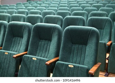 Green chairs in empty cinema auditorium