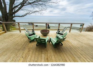 Green chairs surrounding a fire pit on a wooden patio in Prince Edward County, Ontario - Canada. In background some people are enjoying the beach facing the lake.