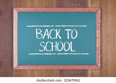 Green chalkboard on wooden background with text Back to School