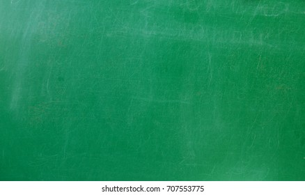 Green chalkboard with scratches in school. Background texture.