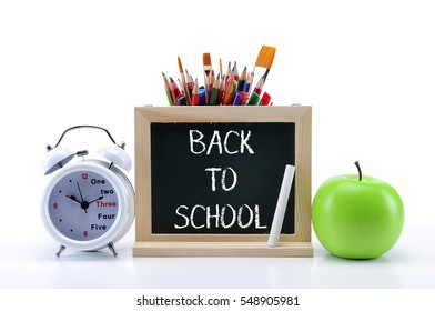 green chalkboard with stationery and a apple on white background
