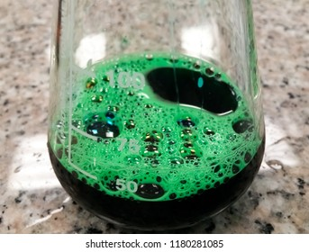 Green chemical inside a glass Erlenmeyer flask. Scientific experiment, bubbling chemical reaction. Toxic, dangerous and flashy.