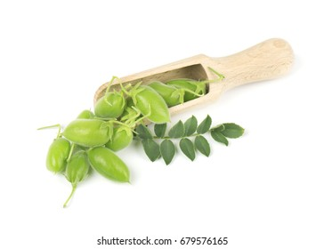 Green chickpeas in the pod on a wooden spoon isolated on white background