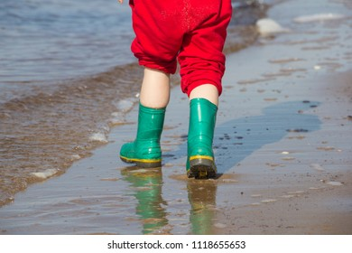 Green children's rubber boots. Walking on water