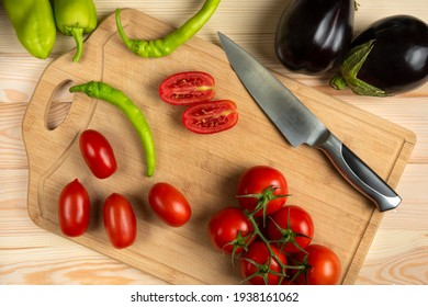 Green chilies and sliced tomatoes on the wooden table
