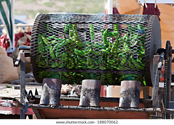 Green chilis are fire roasted in a large metal drum
