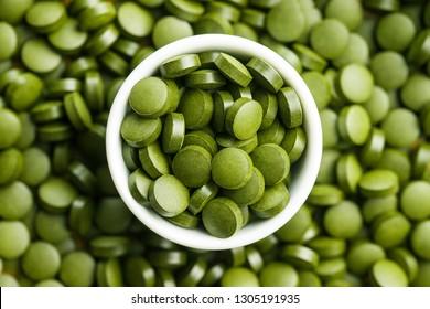 Green chlorella pills or green barley pills in bowl. Top view.