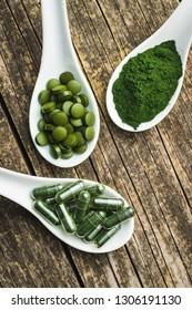 Green chlorella pills or green barley pills and powder in ceramic spoon.