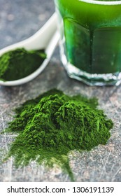 Green chlorella powder and drink on old kitchen table.