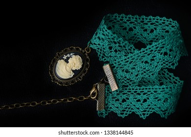Green choker with girl cameo on a dark background close up