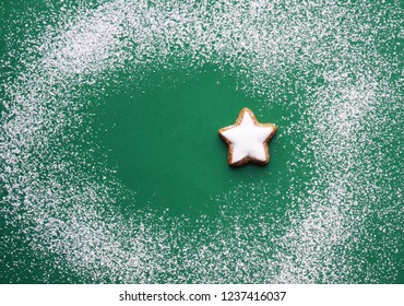green christmas background with powdered sugar as snow and a  star cookie, greeting card with copy space