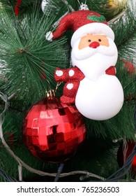 Green Christmas tree decorated with a snowman and a red ball