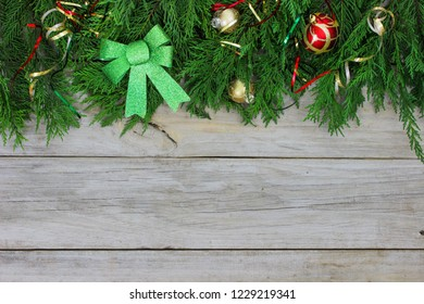 Green Christmas tree garland border with bow, ribbon and red ornaments on antique rustic wood background; blank holiday sign with wooden copy space