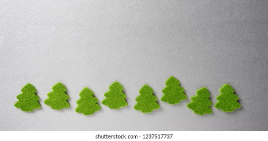 green christmas trees isolated over silver background
