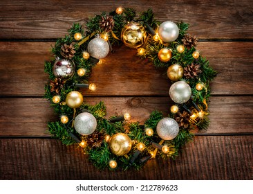 Green christmas wreath decorated with gold balls, lights and pinecones on an old vintage planked wood background - rustic style