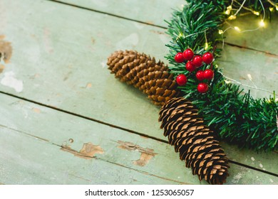Green Christmas wreath with lights and mistletoe and pine cons beside on the old wooden board