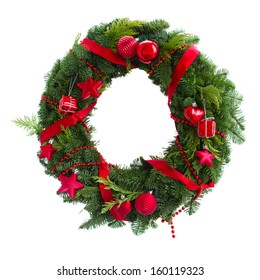 green christmas wreath with red decorations isolated on white background