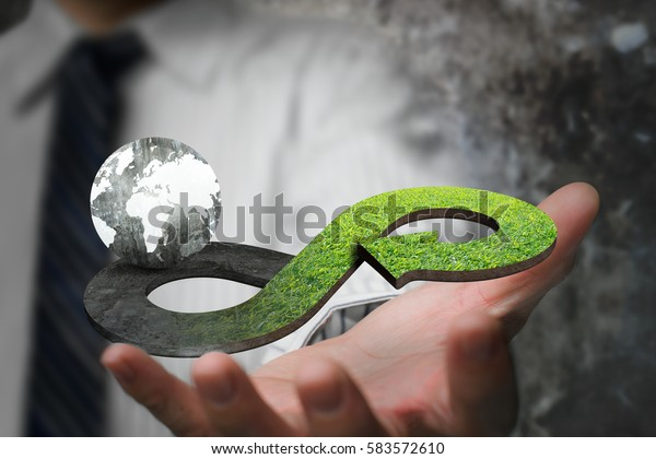 Green circular economy concept. Hand showing arrow infinity symbol with grass texture and globe.